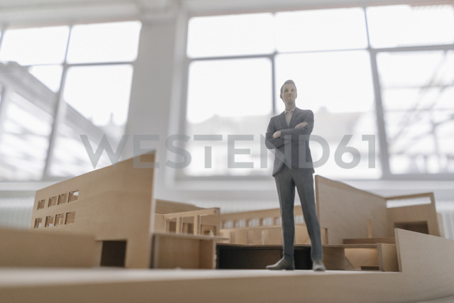 Miniature businessman figurine standing in architectural model - FLAF00120