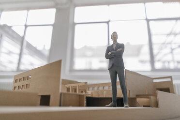 Miniature businessman figurine standing in architectural model - FLAF00120