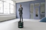 Miniature businessman figurine standing on smart home loudspeaker - FLAF00123