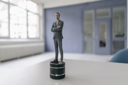 Miniature businessman figurine standing on smart home loudspeaker - FLAF00123