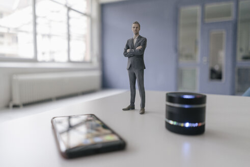 Miniature businessman figurine standing next to smart home loudspeaker and smartphone - FLAF00126