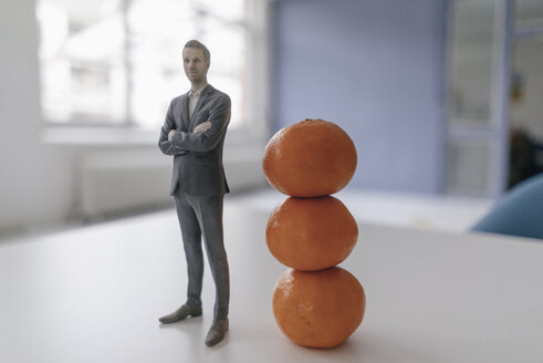 Miniature businessman figurine standing next to clementines - FLAF00129