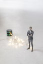 Miniature businessman figurine standing next to smart home loudspeaker with chain of lights - FLAF00132