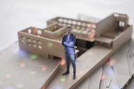 Miniature businessman figurine standing in architectural model with points of light - FLAF00135