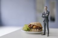 Miniature businessman figurine standing next to fast food - FLAF00138