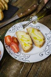 Preparing bruschetta, olive oil and tomato on plate - GIOF03764