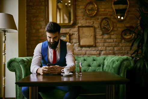 Fashionable young man sitting on couch in a cafe using cell phone - ZEDF01097