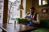 Fashionable young man sitting on couch in a cafe drinking coffee and using cell phone - ZEDF01100