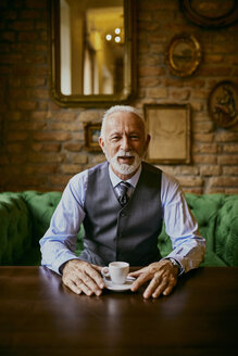 Portrait of elegant senior man sitting on couch in a cafe - ZEDF01106