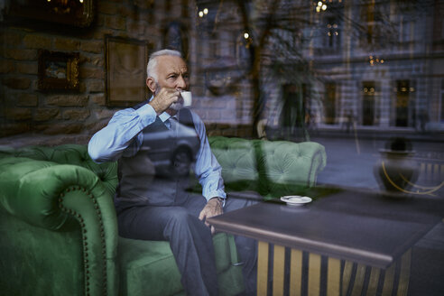 Elegant senior man sitting on couch in a cafe drinking coffee - ZEDF01109