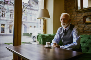 Elegant senior man sitting on couch in a cafe - ZEDF01112