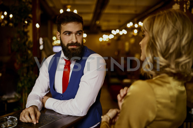 Fashionable young man looking at woman in a bar - ZEDF01118