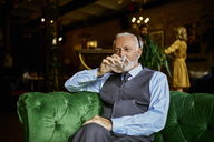 Portrait of elegant senior man sitting on couch in a bar drinking from tumbler - ZEDF01121
