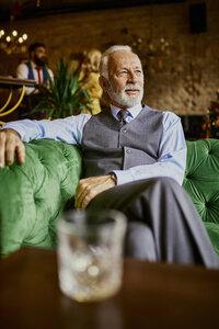 Portrait of elegant senior man sitting on couch in a bar - ZEDF01124