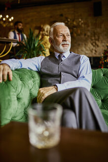 Portrait of elegant senior man sitting on couch in a bar - ZEDF01124
