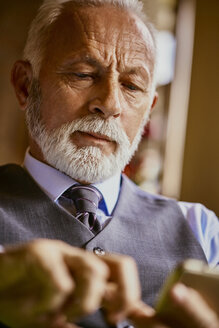 Elegant senior man using cell phone - ZEDF01127