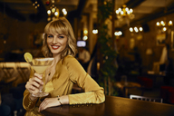 Portrait of elegant woman with cocktail in a bar - ZEDF01133