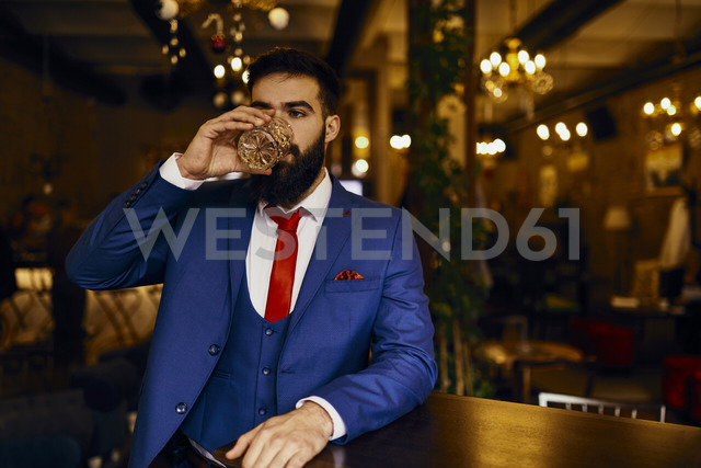 Eegant young man in a bar drinking from tumbler - ZEDF01136