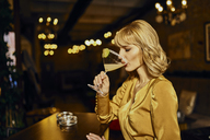 Elegant woman drinking cocktail in a bar - ZEDF01139