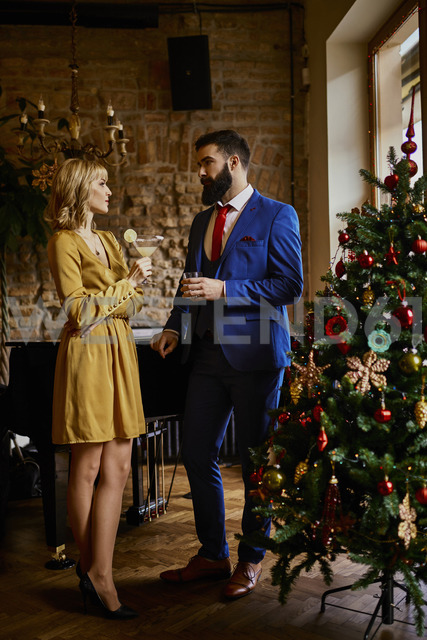 Elegant couple with drinks standing at Christmas tree - ZEDF01148