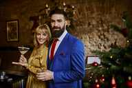 Portrait of elegant couple with drinks at Christmas tree - ZEDF01151