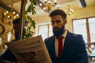 Elegant man reading newspaper in a cafe - ZEDF01175