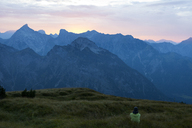 Austria, Tyrol, hiker sitting in alpine meadow at twilight - FAF00076