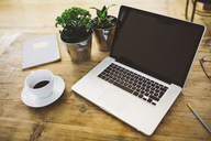 Laptop and a cup of coffee on a table - GIOF03788
