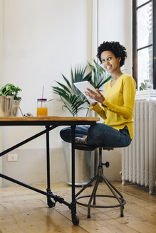 Young woman sitting at home reading on digital tablet - GIOF03806