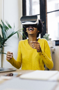 Laughing young woman playing game, wearing virtual reality goggles - GIOF03812
