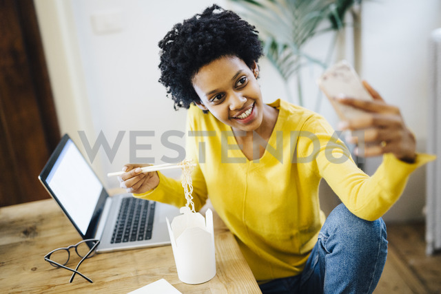 Smiling young woman sitting at table with laptop and noodles, taking a selfie - GIOF03821 - Giorgio Fochesato/Westend61