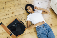 Young woman at home listening vinyl records, lying on ground - GIOF03827