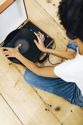 Young woman sitting on grounf listening music from record player - GIOF03830