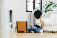 Young woman sitting on grounf listening music from record player, hiding behind vinyl - GIOF03836