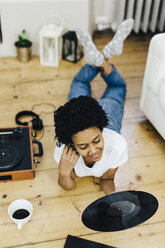 Young woman at home listening vinyl records, lying on ground - GIOF03839