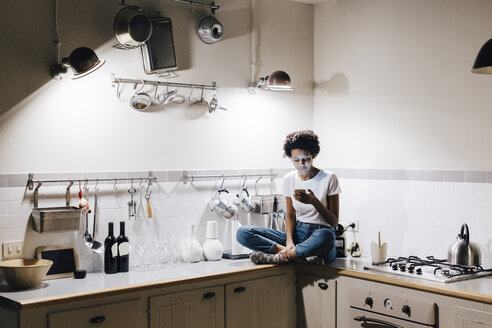 Young woman sitting on kitchen worktop, checking messages on smartphone - GIOF03842