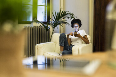 Young woman sitting in armchair, reading smartphone messages - GIOF03845