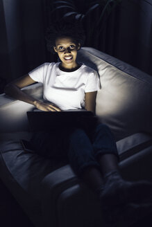Young woman watching online tv at night, using laptop - GIOF03848