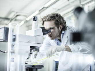 Laboratory technician looking through microscope in lab - CVF00040