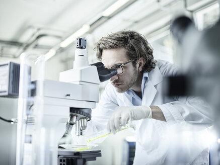 Laboratory technician looking through microscope in lab - CVF00040