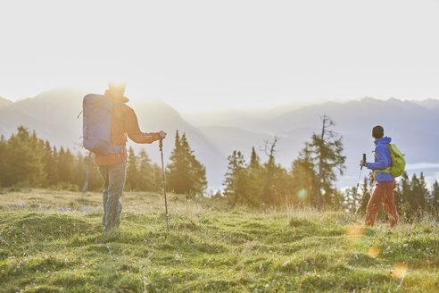 Austria, Tyrol, Mieming Plateau, two hikers on alpine meadow at sunrise - CVF00064