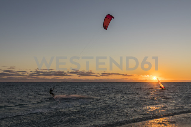 Mauritius, Le Morne, Indian Ocean, kite surfer and sail boarder at sunset - FOF09770