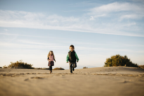 Two children running on the beach in winter - JRFF01529