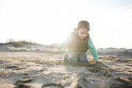 Boy playing with the sand on the beach in winter - JRFF01532