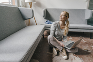 Woman sitting on the floor with laptop - KNSF03549