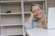 Smiling woman with closed eyes leaning on table with laptop - KNSF03573