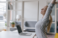 Woman with laptop at desk in office stretching - KNSF03576