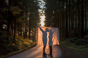 Silhouette of couple holding blanket kissing on country road in forest - WVF00907