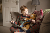 Boy reading a book on couch at home - NMS00196