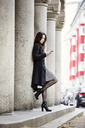 Germany, Cologne, fashionable young woman leaning against column looking at cell phone - JATF00991